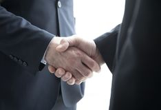 Two businessmen shaking hands. Standing by windows in office Stock Image