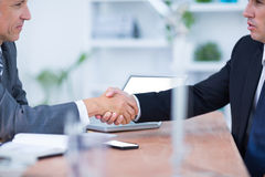 Two businessmen shaking hands and working. In the office Royalty Free Stock Photos