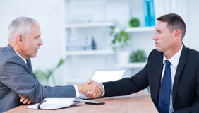 Two businessmen shaking hands and working Royalty Free Stock Photos
