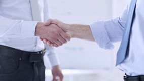 Two businessmen shaking their hands. Business handshake - two businessmen shaking their hands stock footage