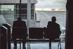 two businessmen silhouettes in airport royalty free stock photos