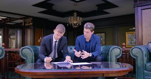 Two businessmen are sitting in beautiful apartments in suits and discussing the signing of the contract, the terms of. Two businessmen are sitting in beautiful stock video