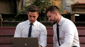 Two businessmen sitting on a bench, using laptop. Two businessmen sitting on a bench in the city, using laptop stock video footage