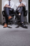 Two businessmen sitting down with legs crossed, low section Royalty Free Stock Image