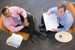 Two businessmen sitting indoors having a meeting. Two businessmen sitting indoors with coffee and a laptop having a meeting Stock Photography