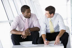 Two businessmen sitting in office lobby talking. And smiling Stock Images