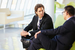 Two Businessmen Sitting On Sofa In Modern Office Stock Photography