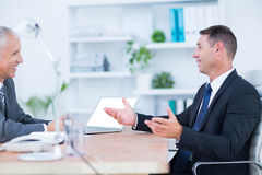 Two businessmen sitting and speaking Stock Images