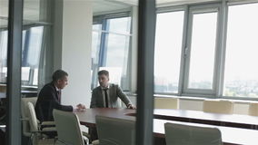 Two businessmen are sitting at a table in a room behind a glass wall. stock video footage
