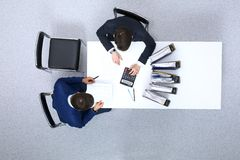 Two businessmen sitting at the table, view from above. Bookkeeper or financial inspector making report, calculating o. R checking balance. Internal Revenue stock photography