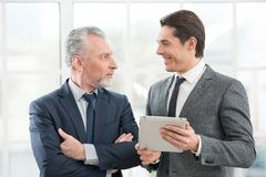 Two businessmen smiling and working on tablet Royalty Free Stock Image