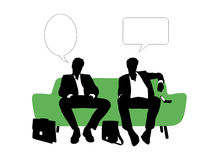 Two businessmen speaking seated on green sofa Stock Images