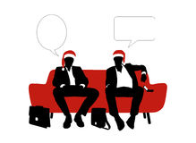 Two businessmen speaking seated on a sofa in red christmas hats Stock Images
