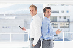 Two businessmen standing back to back. In the office Stock Photos