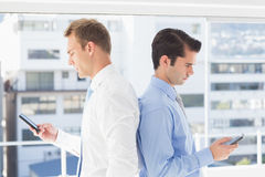 Two businessmen standing back to back. In the office Royalty Free Stock Photo