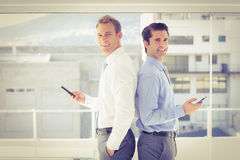 Two businessmen standing back to back. In the office Royalty Free Stock Photos