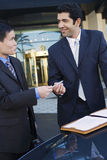 Two businessmen standing beside car outside hotel, man passing pen to colleague with contract, smiling Stock Photos