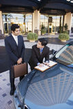 Two businessmen standing beside car outside hotel, man signing contract, smiling Stock Photo