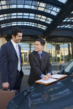 Two businessmen standing beside car outside hotel, man signing contract, smiling Stock Image