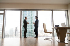 Two businessmen standing at full-length window in office, coffee stock photo