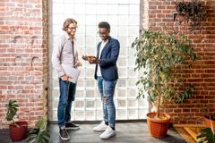 Two businessmen standing in the loft office stock images