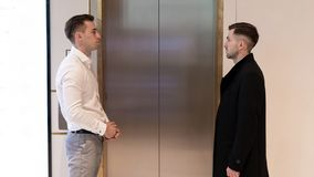 Two businessmen standing near elevator. Business people near a elevator in office stock photography