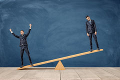 Free Two Businessmen Standing On A Wooden Seesaw, One Happy And One Sad Looking. Stock Photos - 92629313