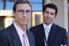 Two businessmen standing outside building, smiling, portrait (differential focus) Stock Photos
