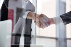 Two businessmen standing and shaking hands in office Stock Images