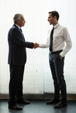 Two businessmen standing up and shaking hands Stock Images
