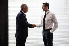 Two businessmen standing up and shaking hands Royalty Free Stock Image