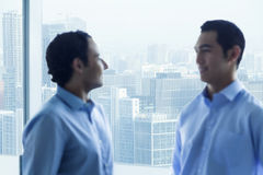 Two businessmen standing by the window and talking in the office royalty free stock images