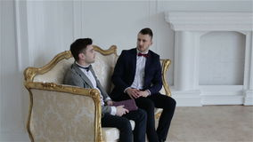 Two businessmen in suits with bow ties are communicating in a beautiful white room with elegant gold sofa. stock footage