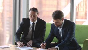 Two businessmen in suits making deal agreement handshake signing contracts. Two businessmen in suits make deal business agreement handshake sign franchise stock footage