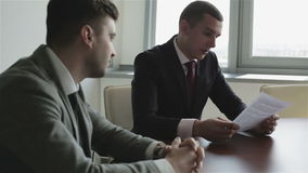 Two businessmen in suits are sitting at a table in front of the window and learning a new contract. stock video