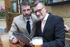 Two businessmen with tablet at a restaurant Stock Image