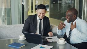 Two businessmen talking ang laughing in modern cafe. Business colleagues having fun and joking looking at laptop. Two businessmen talking ang laughing in modern stock video footage