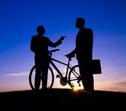 Two Businessmen Talking in Back Lit with Bicycle Stock Images