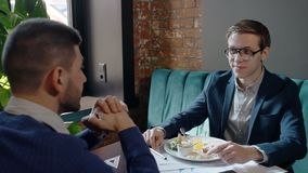 Two businessmen is talking during business lunch, sitting at table in cafe. Two businessmen is talking during business lunch, sitting at table in cafe, young stock video