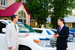 Two businessmen talking about cars. Two businessmen standing and talking about cars with one of them having expression on his face Stock Photo