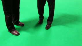 Two businessmen talking on green background. Legs of two men in suits and leather shoes standing near each other on the green color colour floor; businessmen stock video