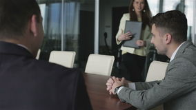 Two businessmen are talking in a meeting room. Beautiful girl secretary is bringing the documents in a black leather folder and putting them on the table stock video