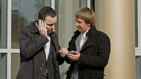 Two businessmen talking on mobile phone and stock video footage