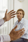 Two businessmen talking in office, focus on man gesturing with hands in foreground Stock Photo