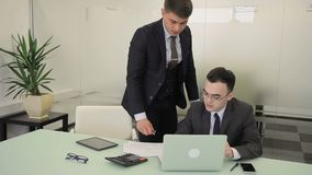 Two businessmen are talking at table in large company. Young people look documents carefully and speak actively, gesticulating with hands, one of them sits at stock footage