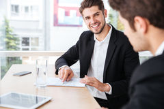 Two businessmen talking and working with documents in office Stock Photos