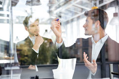 Two businessmen talking and writing on glass board in office. Two concetrated young businessmen talking and writing on glass board in office Royalty Free Stock Image
