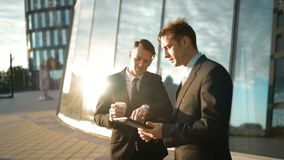 Two businessmen trading outdoor. Two Young successful businessmen bidding and discuss their deal and trade. First offer his variation with tablet PC. Second stock footage