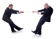 Tug of war. Two businessmen in a tug of war isolated on white background stock images