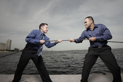 Two businessmen tugging on a chain. Image of two businessmen pulling at a metal chin stock image